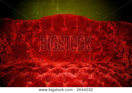 a read velvet couch with a green backgroung poster