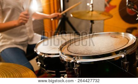 Repetition. Ginger girl plays on drums in the studio. Focus on drums poster