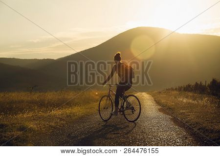 Cycling In Sunset. Lifestyle Concept. Hipster Woman Cycling In Sunset In Countryside. Healthy Lifest