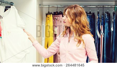 Happy Woman Shopping In Clothing Store. Sale, Fashion, Consumerism And People Concept. Young Woman C