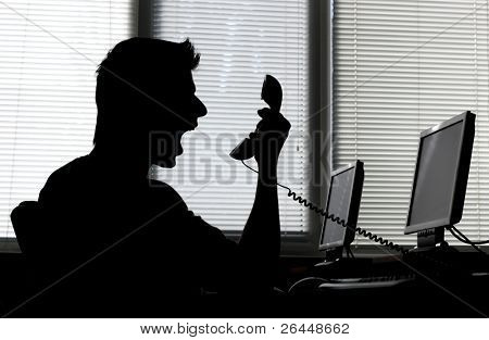 Silhouette of an angry man shouting into the phone receiver in his office