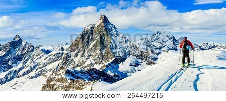 Man skiing on fresh powder snow. Ski in winter season, mountains and ski touring backcountry equipments on the top of snowy mountains in sunny day with Matterhorn in background, Zermatt in Swiss Alps. poster