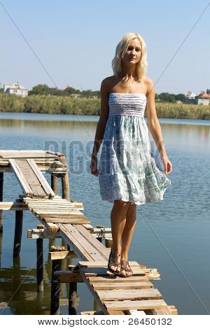 Girl walking along the pier on a hot sunny day