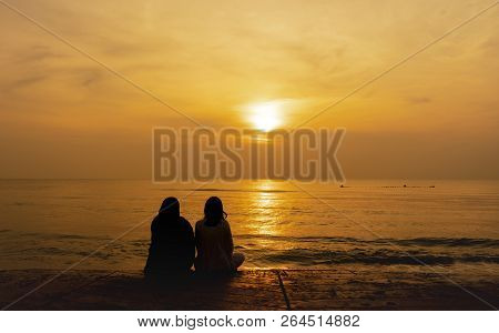 Silhouette Of A Women Sitting On The  Beach And Looking Sunrise Over The Sea