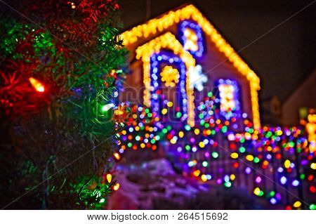 Spruce Branches With Christmas Ornaments On The Background Of A House With Christmas Lights. Christm