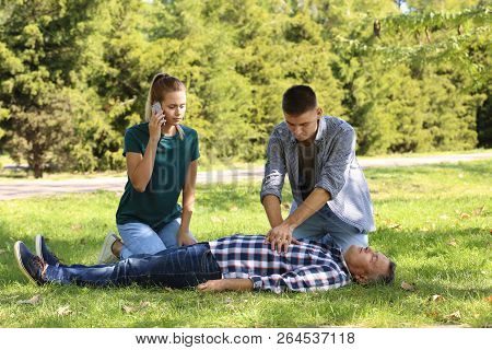 Passersby Helping Unconscious Man Outdoors. First Aid