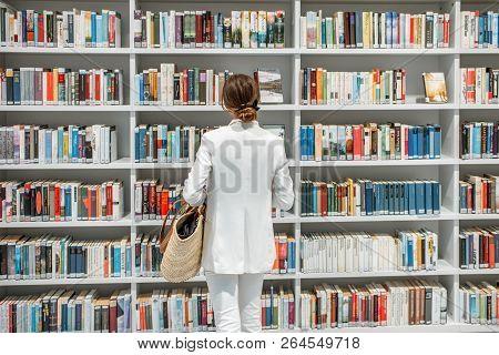 Stuttgart, Germany - August 10, 2017: Woman Standing Near The Bookshelves In The Stuttgart City Libr