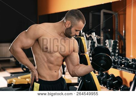 Strong Young Man Lifting Dumbbell In Gym