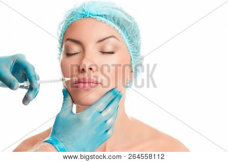 Young beautiful woman getting ready for lips augmentation, plastic surgery, doctor's hand in blue gloves injecting hyaluronic acid or botulinum toxin in her lips isolated on white background. poster