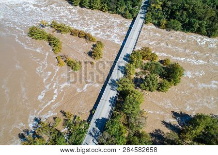 Austin Flood Waters rush down the Colorado River under Bridge at Red Bud Isle towards Longhorn Dam aerial drone view looking straight down about flooded river in Austin , Texas , USA poster