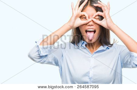 Young asian business woman over isolated background doing ok gesture like binoculars sticking tongue out, eyes looking through fingers. Crazy expression.