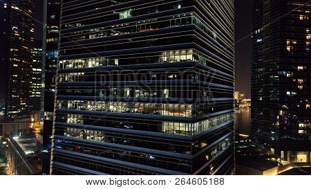 Exterior Of Modern Skyscrapers With Luminous Windows Of Offices Of Megapolise In Evening. Shot. Conc
