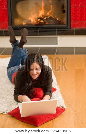 Home living happy young woman by fireplace working on laptop