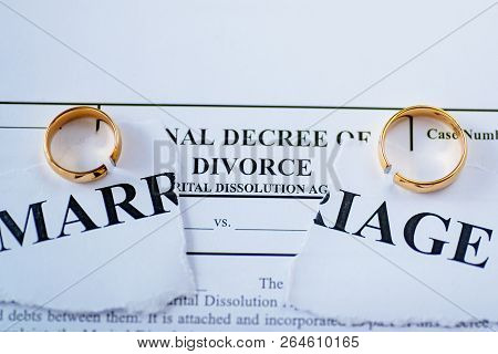 Divorce Decree And Two Broken Wedding Rings. Divorce And Separation Concept