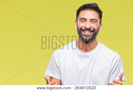 Adult hispanic man over isolated background success sign doing positive gesture with hand, thumbs up smiling and happy. Looking at the camera with cheerful expression, winner gesture.
