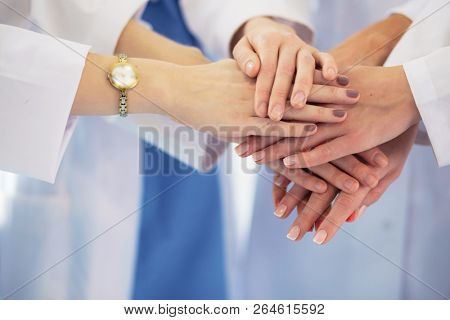 Doctors and nurses in a medical team stacking hands.