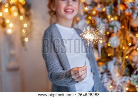 Little Girl With Sparkler Near Christmas Tree On Christmas Eve At Home. Young Kid In Light Bedroom W