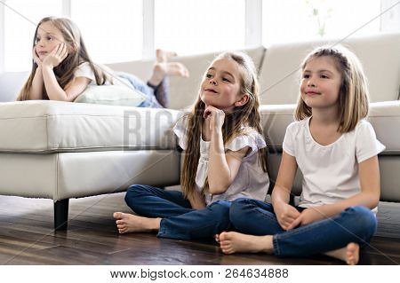 Three Attractive Teenage Girls In Casual Clothes Watching Tv At Home