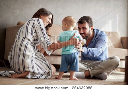 happy family is having fun playing with a baby at home