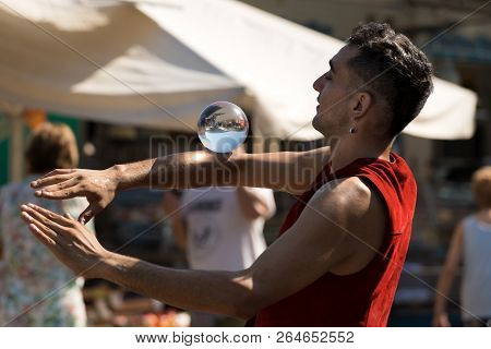 Lerici, Liguria, Italy, July 19, 2014: Unidentified Young Juggler With A Crystal Ball, Shows His Art