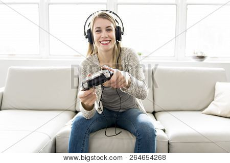 Beautiful Young Woman Sitting On Sofa With Game Controller