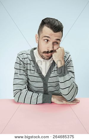 Serious, Bored And Dull Business Man Sitting At Table On Blue Studio Background. The Portrait In Min