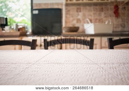 blurred kitchen interior - focus on old white tablecloth