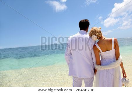 Just-married couple standing by blue lagoon