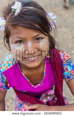 MANDALAY, MYANMAR - MARCH 12 : Unidentified Burmese girl with traditional thanaka on her face on March 12, 2016 in Mandalay, Myanmar.Thanaka is a yellowish-white cosmetic paste made from ground bark