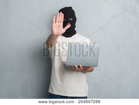 Young caucasian hacker man over grey grunge wall doing cyber attack using laptop with open hand doing stop sign with serious and confident expression, defense gesture