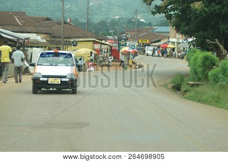 Abetifi, Ghana: July 18th 2016 - Car Driving On Typical Town Street In Ghana, West Africa