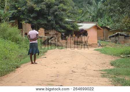Abetifi, Ghana: July 18th 2016 - A Young Girl Standing Stationary On A Dirt Road In Ghana, Looking T