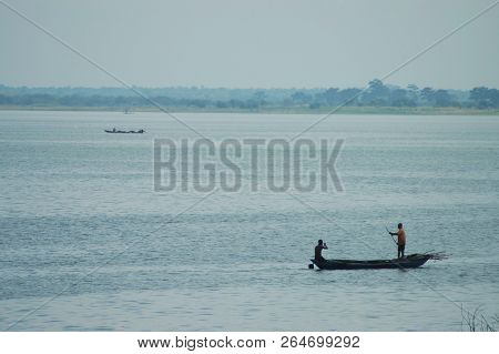 Donkorkrom, Ghana: July 20th 2016 - People In A Wooden Canoe Out Fishing On The Water In Ghana, West