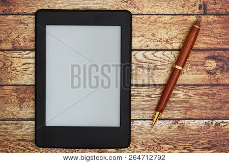 A Blank E-reader On A Old Desk With A Pen That You Can Use As A Mock Up For Your Message