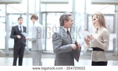 Businessman And Assistant Discussing Working Issues.photo On Blurred Office Background