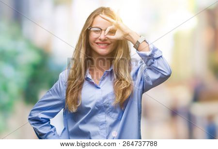 Young beautiful blonde business woman wearing glasses over isolated background doing ok gesture with hand smiling, eye looking through fingers with happy face.