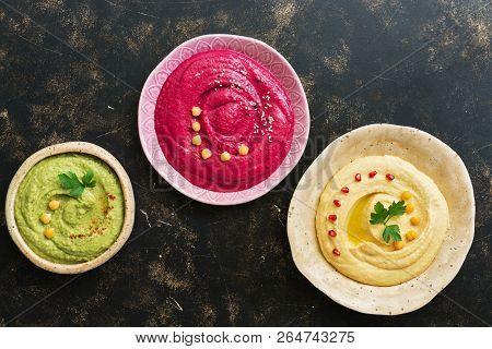 A Variety Of Colored Hummus, Classic Hummus, Beet Hummus, Hummus With Avocado On A Dark Rustic Backg