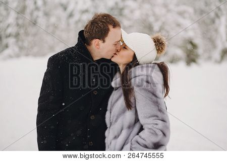 Stylish Couple In Love Gently Kissing In Snowy Mountains. Portraits Of Happy Family Gently Embracing