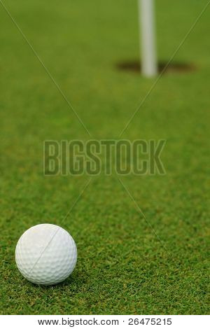 Golf ball in front of the hole
