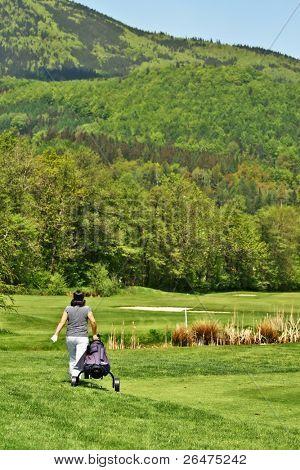Golfer on golfcourse with golf bag