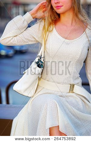 Fashion woman in autumn spring dress with flared skirt on city street. Female style of feminine fashionable girl model with beautiful lips fall outdoor. Color tone on shiny sunlight background.