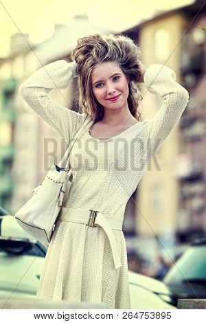 Fashion woman in autumn spring white dress on city street. Female style feminine fashionable girl model with outdoor. Color tone image sepia car and building on shiny sunlight background.