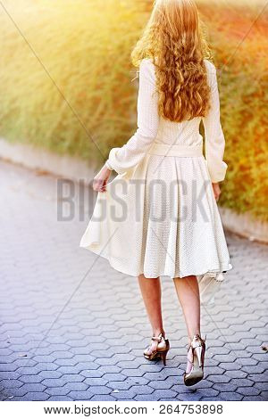 Fashion woman in autumn spring dress on city street . Back of female style of feminine fashionable girl model wallking cobblestone pavement outdoor. Color tone on shiny sunlight background.