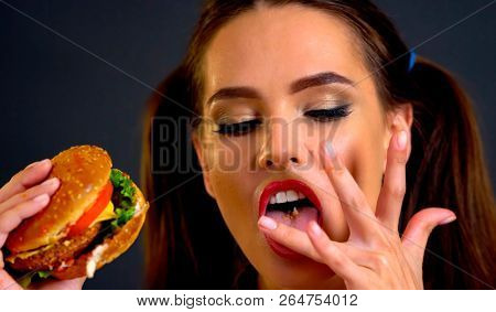 Woman bite big hamburger and lick your fingers after eating. Proper nutrition improves health. Portrait of person with good appetite have greedily dinner. As there is something that you want and do