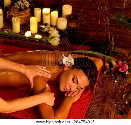 Aromatherapy massage of woman in spa salon. Girl on candles background treats problem health . Luxary interior with working masseuse. Indian back treatment as pain relief for female. Top view.