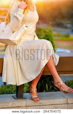 Fashion woman in autumn spring dress with flared skirt on city street. Female style feminine fashionable girl model with slender legs in sunset fall outdoor. Color tone on shiny sunlight background.