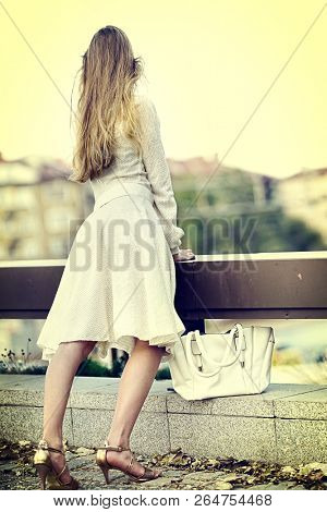Fashion woman in autumn spring dress on city street. Sosial isoltion female style of feminine fashionable girl model wallking outdoor. Color tone on shiny sunlight background. Color tone on shiny