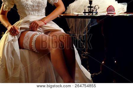 Bride wedding garter. Wedding night preparing garter. Bride undressing and put veil on table. Candle illuminates house. Girl choosing stocking before wedding. Role-playing game in bride.