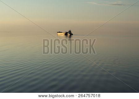 The Golden Ship On The Lake At Sunset. The Setting Sun Illuminates The Barge On The Lake. The Horizo