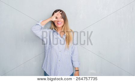 Young adult woman over grey grunge wall wearing fashion business outfit doing ok gesture with hand smiling, eye looking through fingers with happy face.